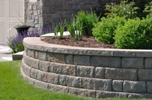 Rounded retaining wall with plants and mulch