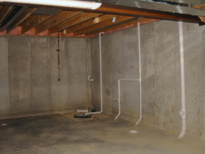 Picture of a basement with a sump pump in the corner.