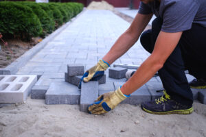 Picture of a man installing patio pavers.